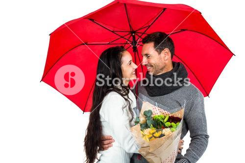 Smiling couple holding umbrella and bouquet