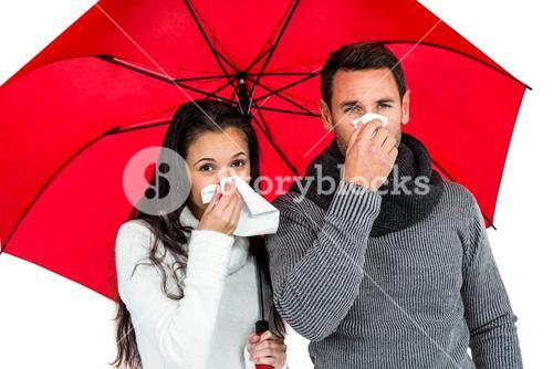 Couple under umbrella blowing their noses