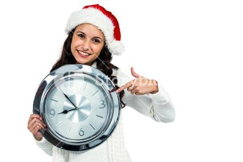 Attractive woman with christmas hat holding clock