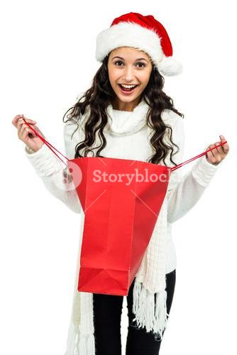 Happy woman with christmas hat opening red shopping bag