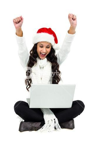 Woman sitting on the floor rejoicing looking at laptop