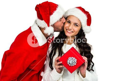 Couple with christmas hats holding red gift box