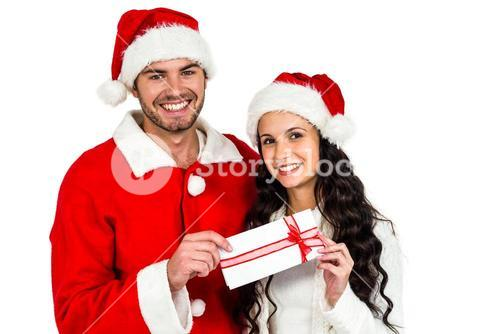 Couple with christmas hats holding gift box
