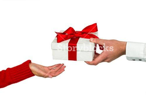 Cropped hand of man giving gift to woman