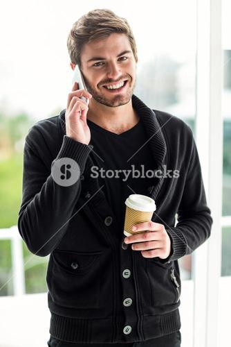 Handsome man on phone call holding disposable cup