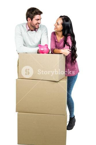 Smiling couple holding on boxes with piggy saver