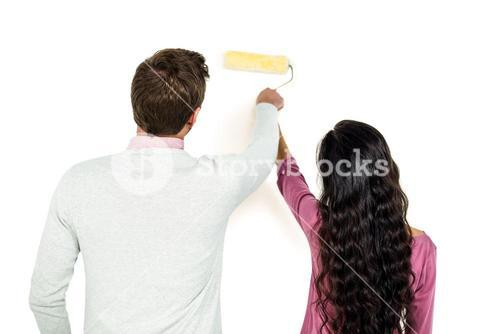 Rear view of couple holding paint roller