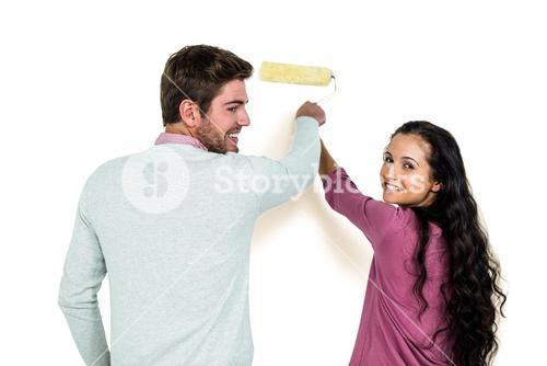 Smiling couple holding paint roller