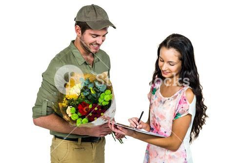 Woman signing for bouquet delivery with smiling postman