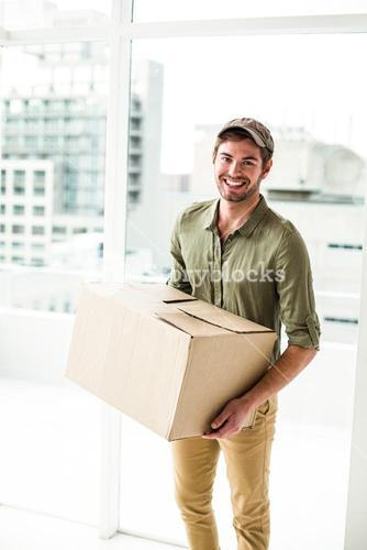 Smiling postman holding package