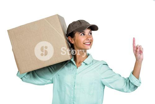 Happy delivery woman holding box pointing up
