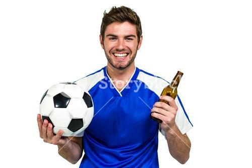 Smiling man holding football and beer bottle