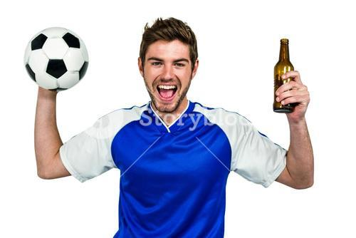 Portrait of excited man holding football and beer bottle