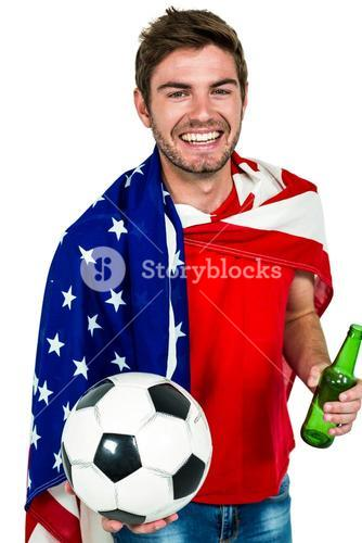 Smiling man holding football and beer bottle wearing American flag