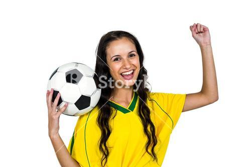 Stylish supporting woman holding football ball rejoicing