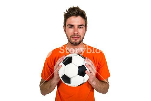 Handsome supporter holding football ball