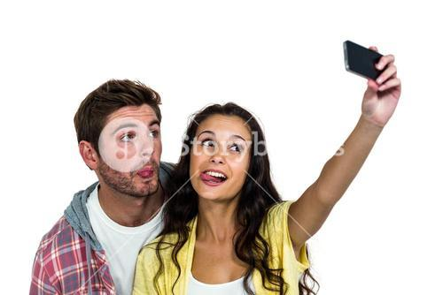 Couple sticking out tongue while taking selfie