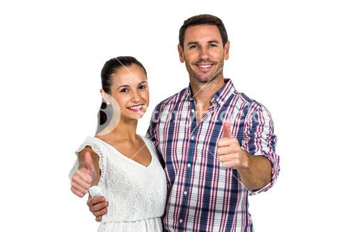 Smiling couple showing thumbs up at camera