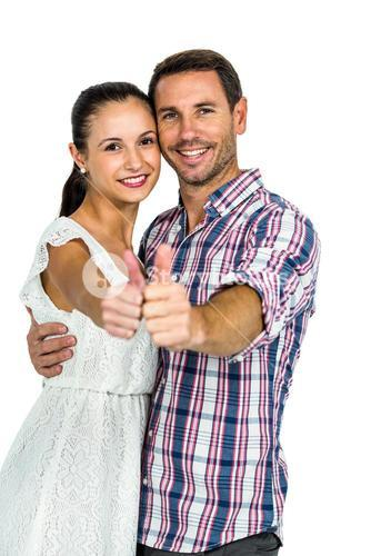Young couple showing thumbs up at camera