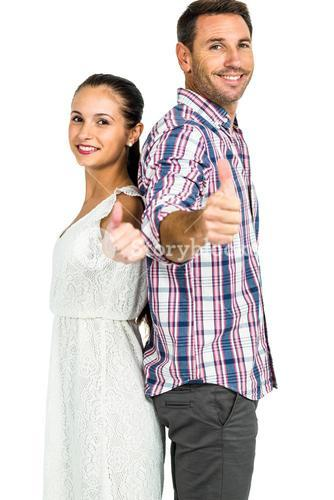 Smiling couple standing back to back showing thumbs up