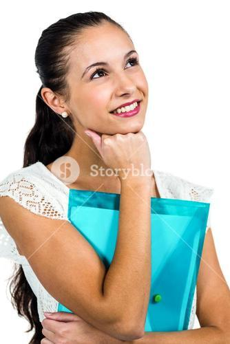 Smiling thoughtful woman holding plastic folder with fist on chin