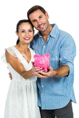 Smiling couple holding piggybank