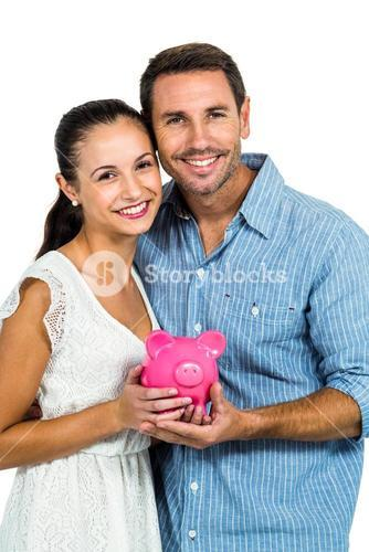 Excited couple holding piggybank