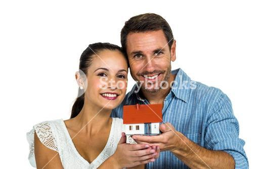 Excited couple holding house model
