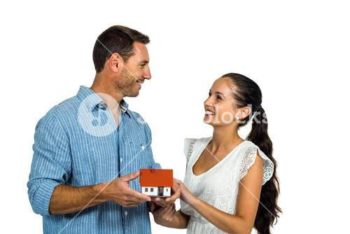 Face to face couple holding house model