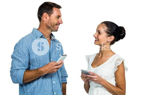 Smiling couple holding smartphones and looking at each other