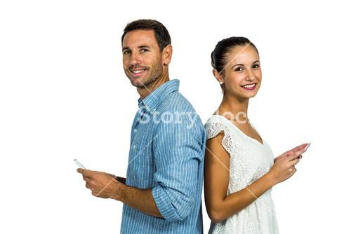 Smiling couple standing back to back using smartphones