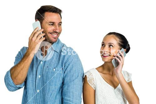 Smiling couple on phone call looking at each other