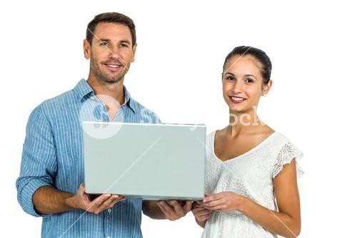 Young couple holding laptop and looking at camera
