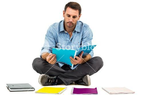 Man sitting on the floor reading notepad
