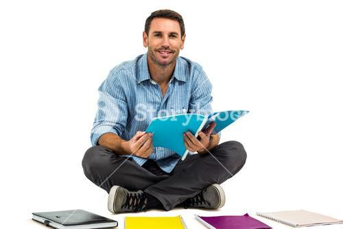Portrait of man sitting on the floor holding notepad