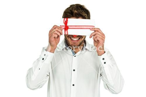 Handsome man covering eyes with gift box