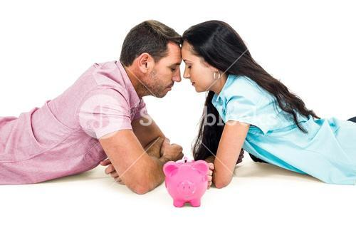 Couple laying on the floor face to face with piggybank
