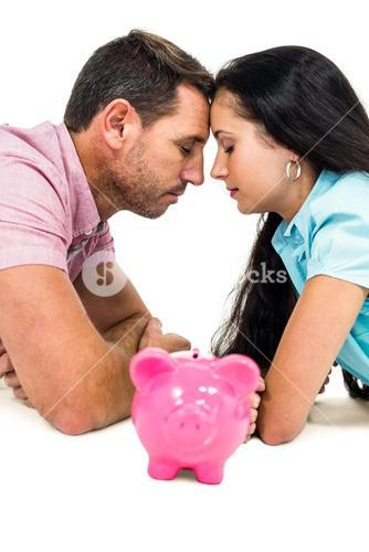 Young couple laying on the floor face to face with piggybank