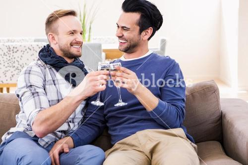 Gay couple toasting on the couch