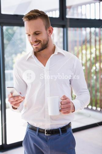 Smiling man with mug and smartphone