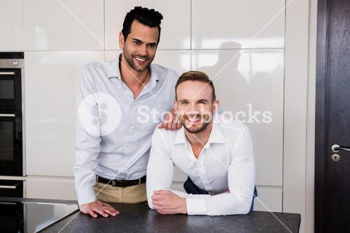 Smiling gay couple in the kitchen