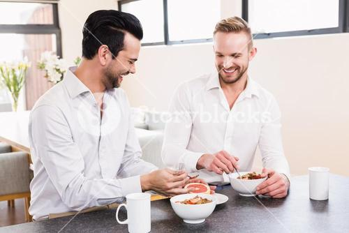 Smiling gay couple having breakfast