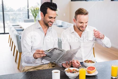 Smiling gay couple reading newspaper