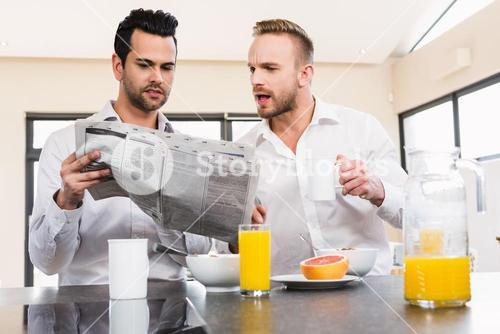 Concentrated gay couple reading newspaper