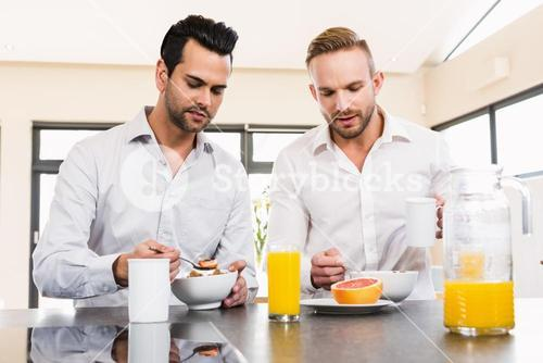 Unsmiling gay couple couple having breakfast