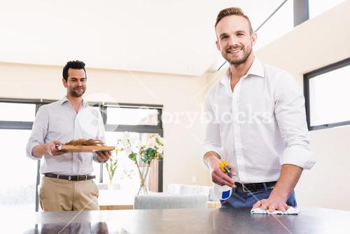 Smiling gay couple cleaning living room