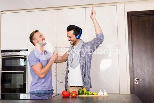 Smiling gay couple having fun while preparing food