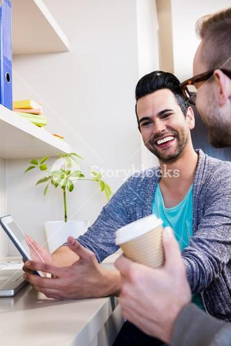 Happy gay couple using tablet