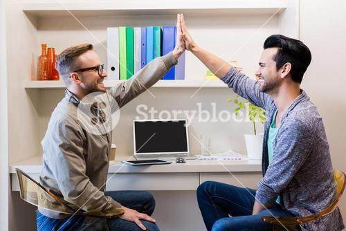 Happy gay couple doing high five