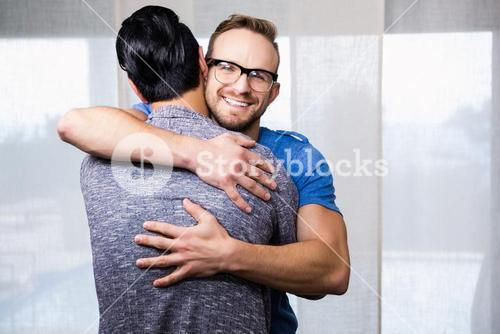 Smiling gay couple embracing